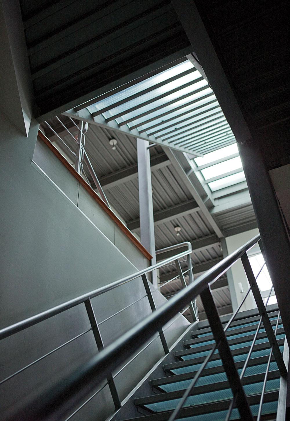 L'escalier aurait du être en inox, affirme le propriétaire, mais aurait coûté dans les six chiffres. Il est donc en acier, comme le plafond et d'autres éléments de la maison. À remarquer, les marches en verre trempé et l'absence de contre-marche.