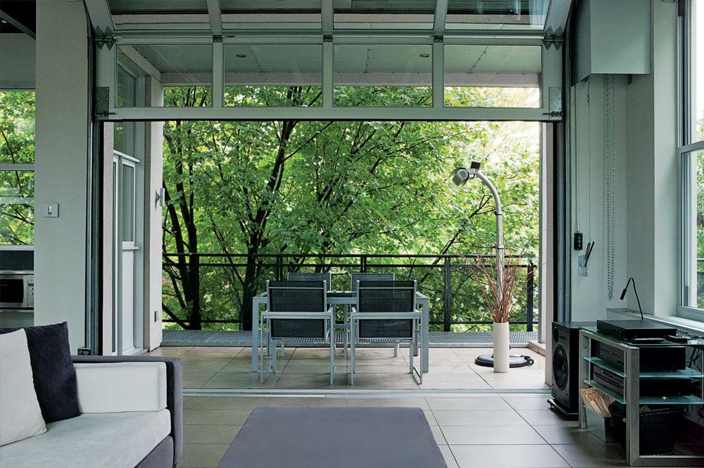 Élément spectaculaire et inattendu de l'aménagement : une porte de garage s'ouvre sur la loggia. L'air circule, le regard se perd, l'extérieur s'invite en dedans. Pour les jours un peu plus frais, un chauffe-patio prend le relais. À noter : le sol en céramique (Ceragrès) continue dehors et le mobilier garde l'esprit du lieu.
