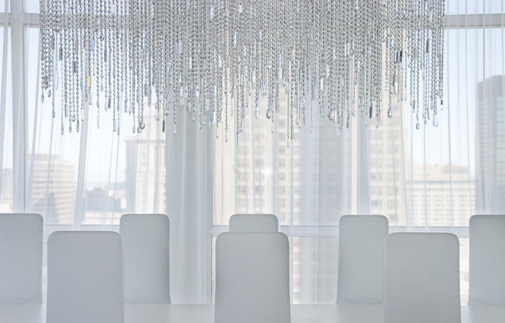 Sous une suspension verre de Swarovski faite sur mesure par Lumidéco, selon les désirs de la propriétaire, les dossiers des chaises montent la garde.