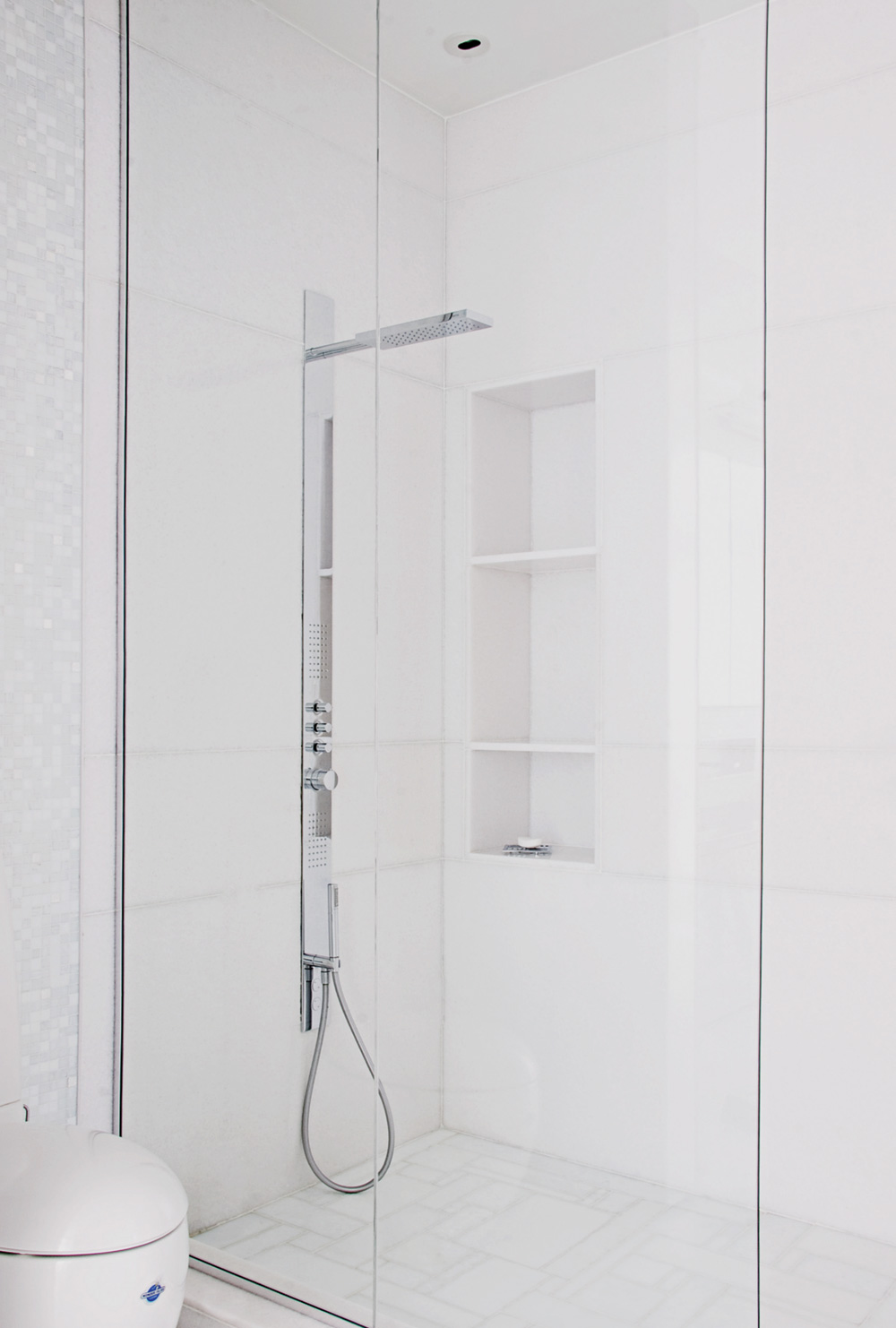 A minimalist shower of marble and glass stands beside an Alessi-Laufen toilet (Batimat) with its WonderGliss technology for easy cleaning.