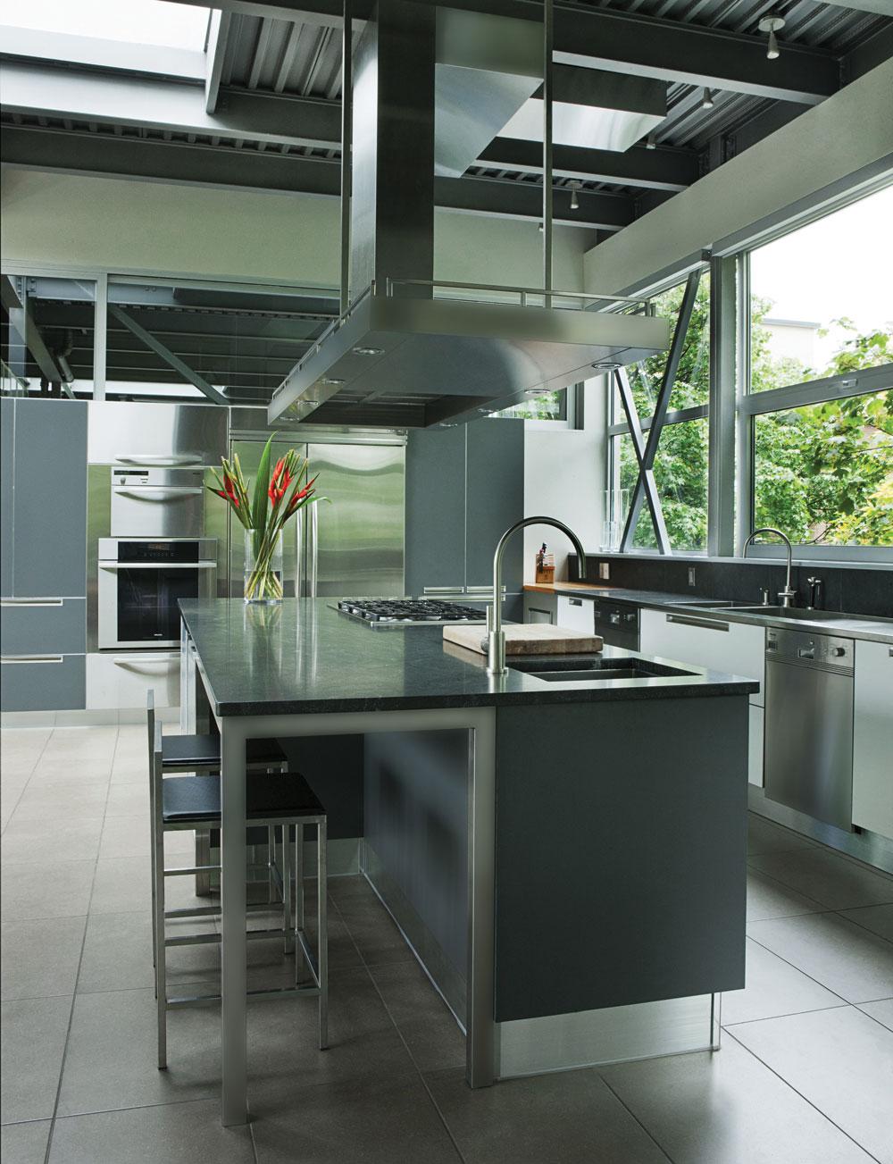 La cuisine, de fabrication italienne (Cuisilab), est un mélange de teintes de gris, d'inox (électroménagers de JC Perreault) et de granit, avec une hotte sculpturale faite sur mesure.