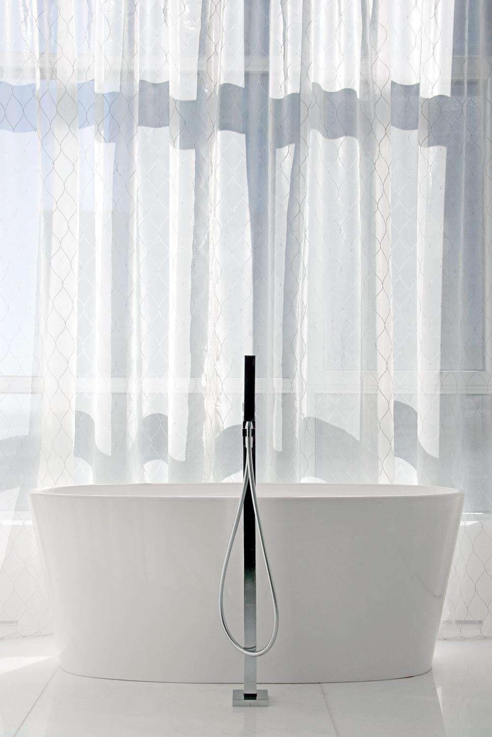 Une baignoire autoportante et sa robinetterie sur pied (Batimat) ont un air théâtral devant un immense rideau pour le rituel du bain.
