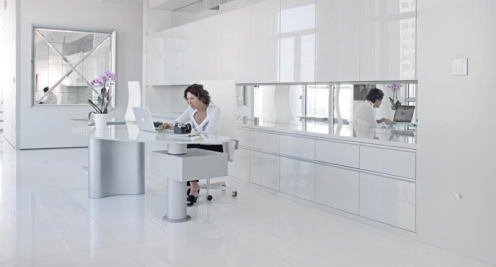 Denyse Abraham à son bureau (Bonaldo) devant tout un mur de rangement séparé en son centre par un miroir. Plus loin, un autre carré et en alu : Osmond Mirror de Pietro Derossi pour Driade Kosmo.