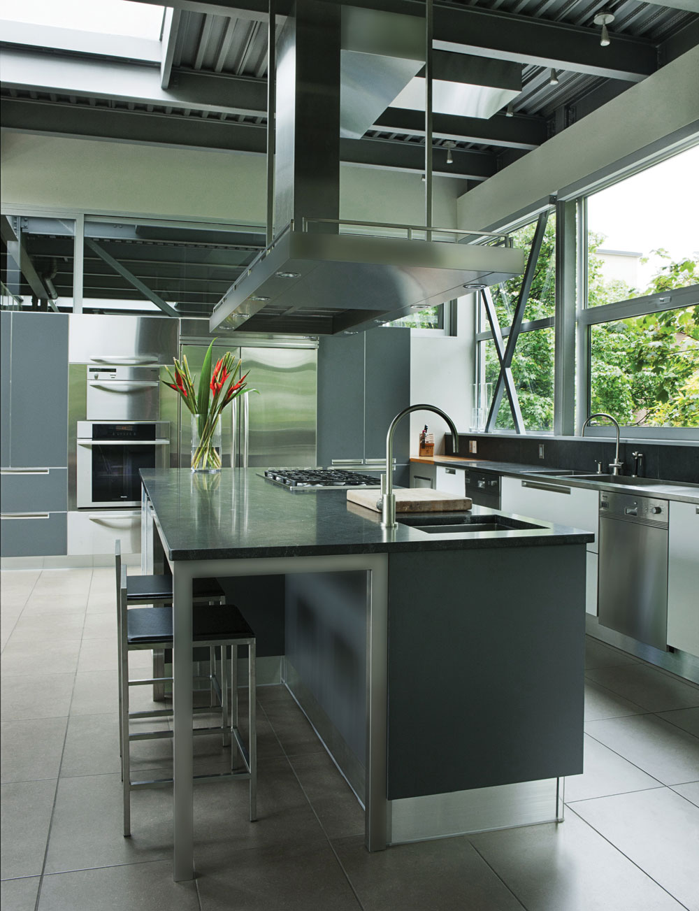 The Italian-made (Cuisilab) kitchen is a mixture of shades of gray, stainless steel (JC Perreault appliances) and granite, with a custom-designed sculptural hood.