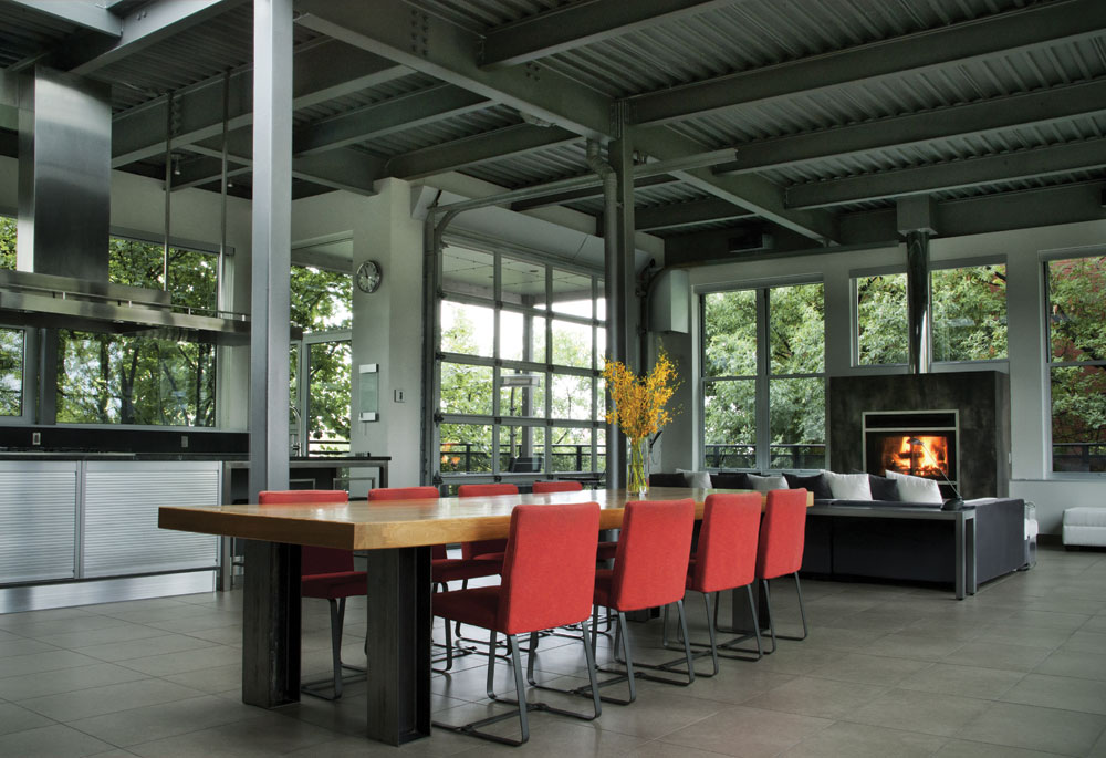 In one very open and airy space are the kitchen, dining room and living room under a steel ceiling. Numerous windows and a forest of trees break the coldness of the metal, the ceramic, the stainless steel and the gray. The touch of red, the owner's favorite color, and the fireplace help create the same effect. As if all this light wasn't enough, a skylight was even added!