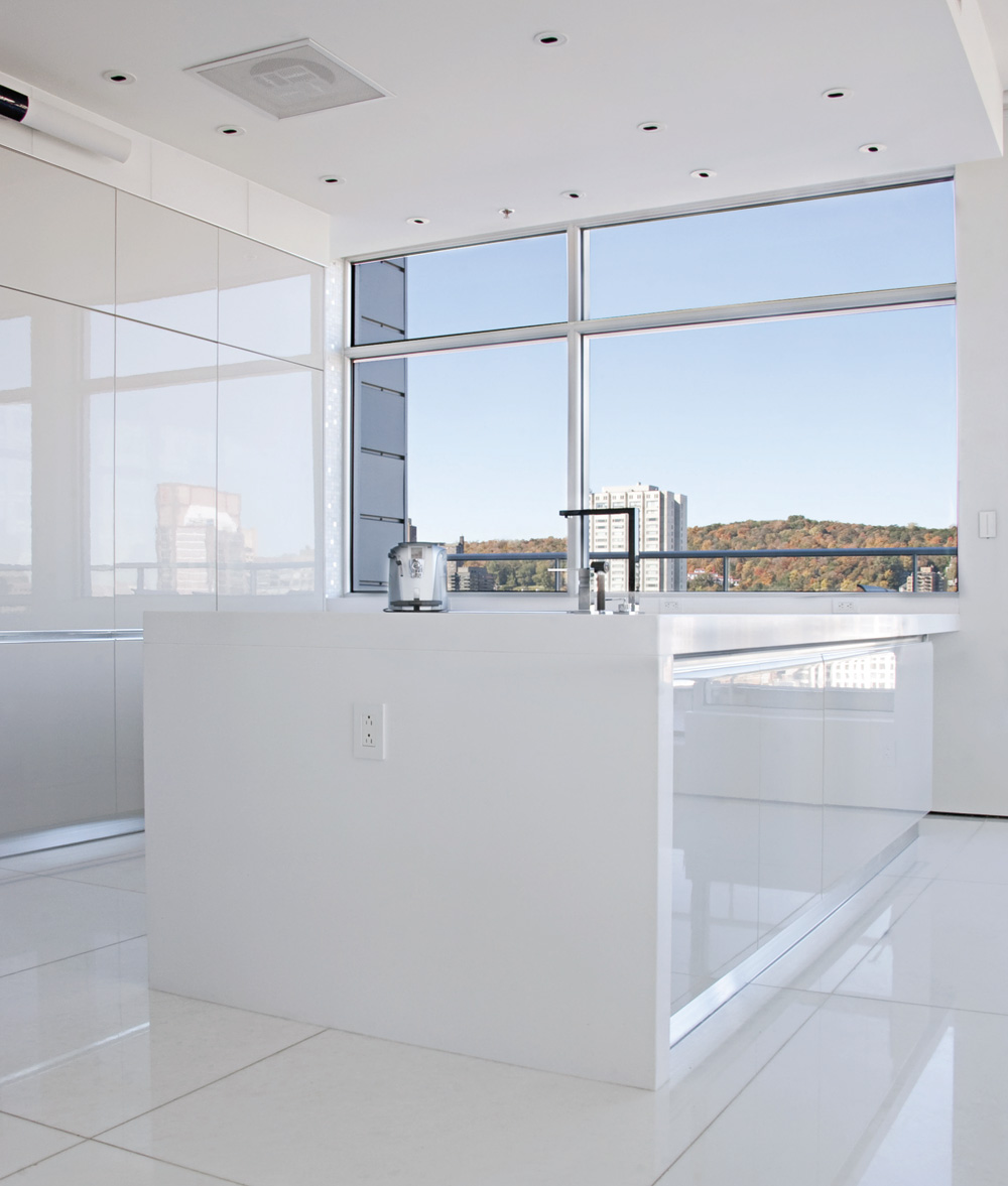 An Italian kitchen (Cuisilab), displaying little more than the taps (Batimat) and a coffee maker (Saeco), is discerned amidst a sea of white. Everything is smooth and shiny. The lights are recessed; the music is too, thanks to a centralized audio system that plays music throughout the condo (Kébecson).
