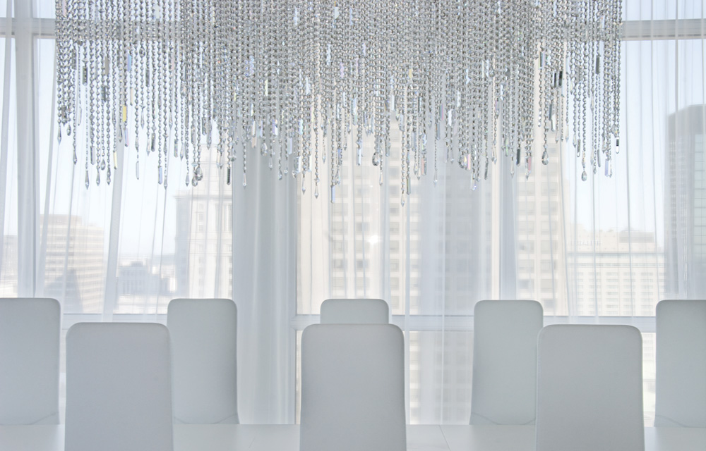 Chair backs stand on guard under a Swarovski chandelier, custom made by Lumidéco according to the owner's specifications.