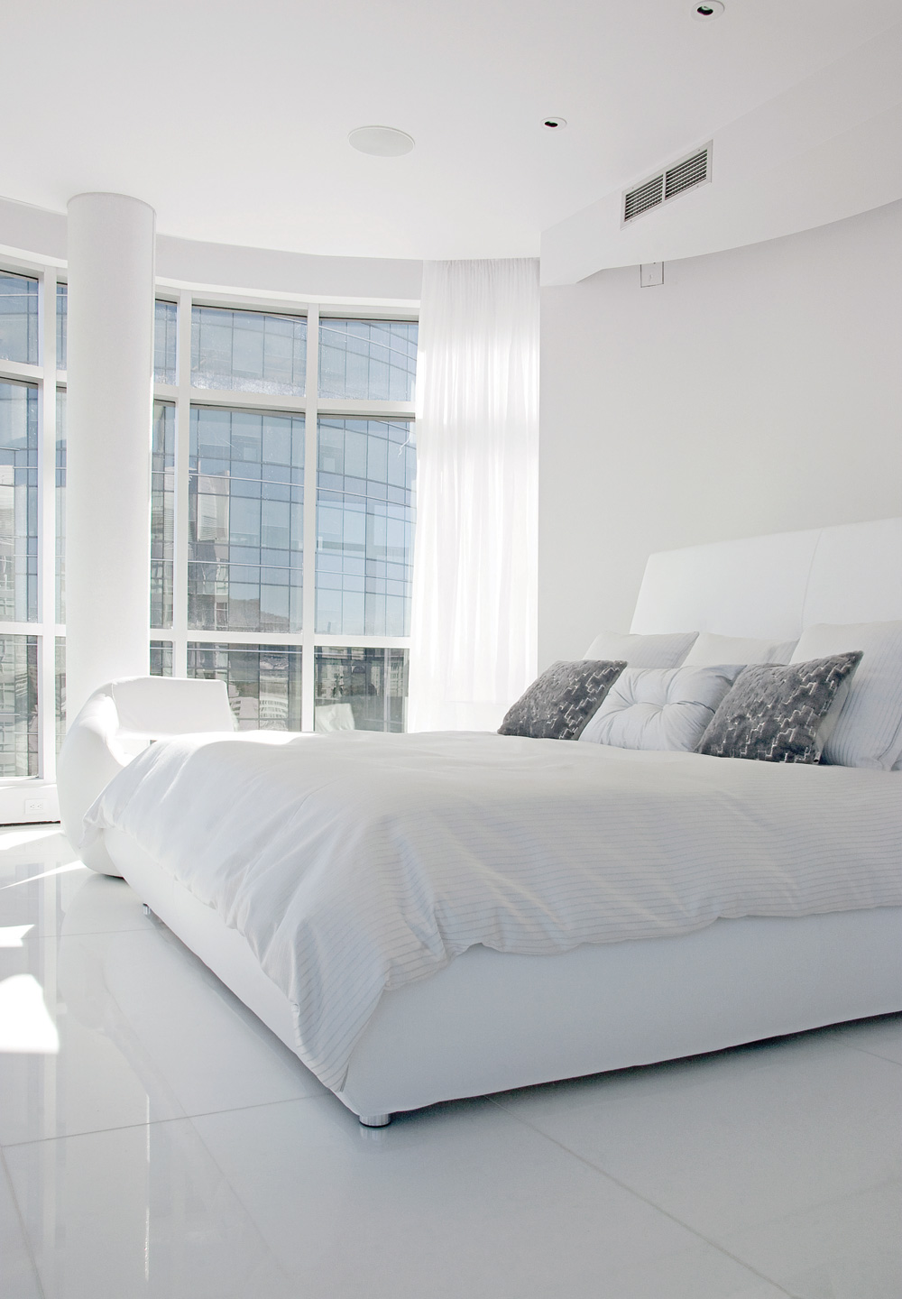 The bed (Bonaldo) with city and river views has cushions and a duvet cover chosen and custom-made by Anne Bondarenko. Unlike the translucent window treatments found throughout the apartment, these ones are opaque for obvious reasons.